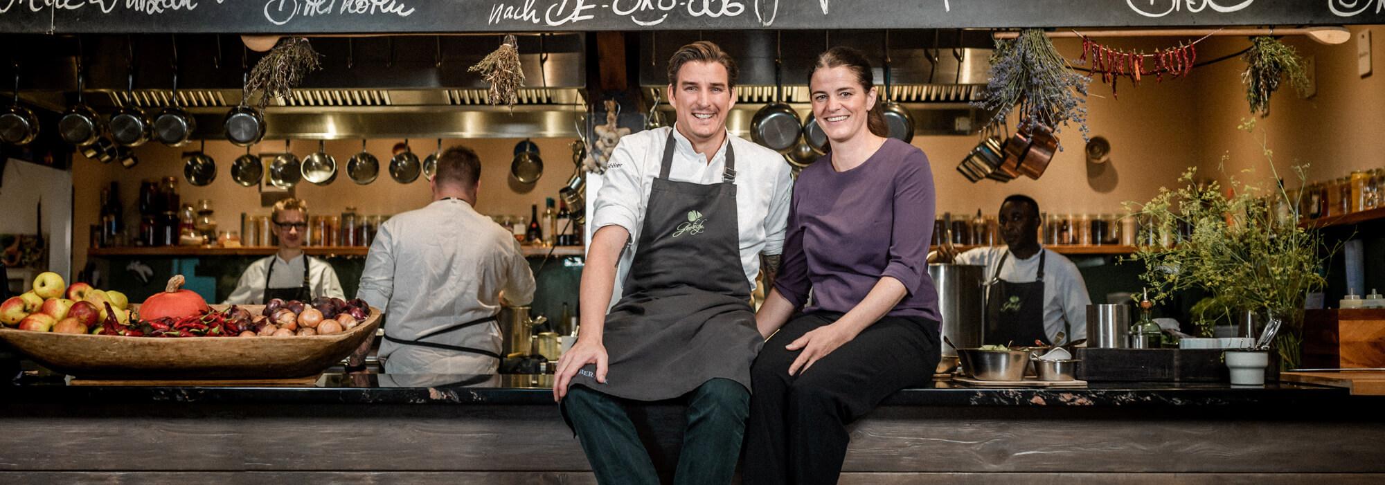 Matthias und Rebecca Gfrörer vom Bio-Restaurant Gutsküche sitzen auf dem Küchentresen.